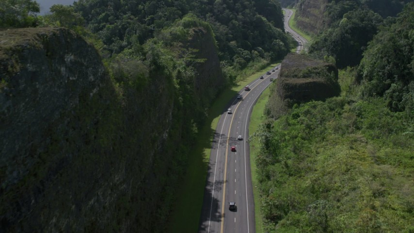 5k stock footage aerial video Following light traffic through lush green mountains, Karst Forest, Puerto Rico Aerial Stock Footage | AX101_082