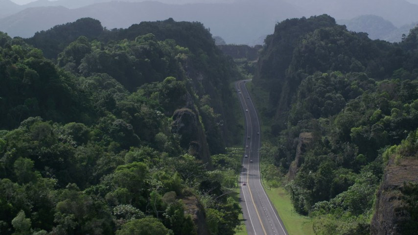 5k stock footage aerial video Flying above highway cutting through lush green mountains, Karst Forest, Puerto Rico Aerial Stock Footage | AX101_085