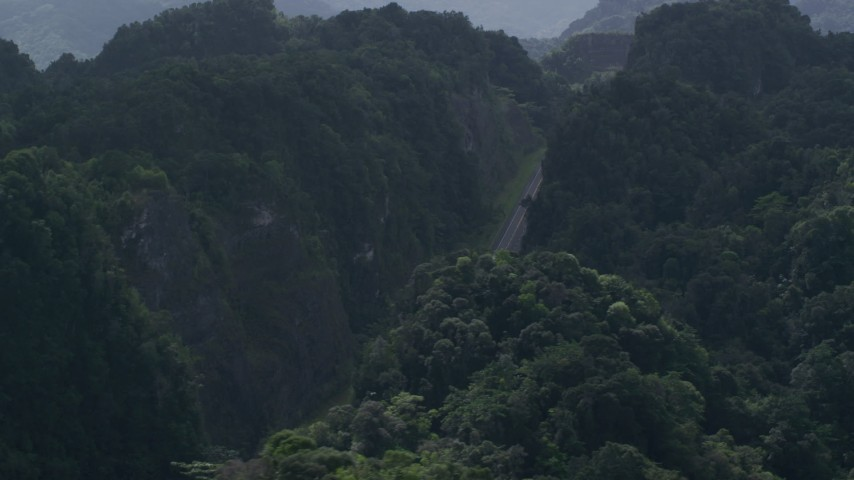 5k aerial video Flying away from a highway cutting through lush green mountains, Karst Forest, Puerto Rico Aerial Stock Footage | AX101_086