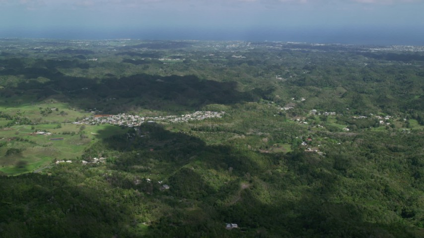 5k stock footage aerial video of Rural homes situated among lush green trees in Karst mountains, Arecibo, Puerto Rico  Aerial Stock Footage | AX101_124