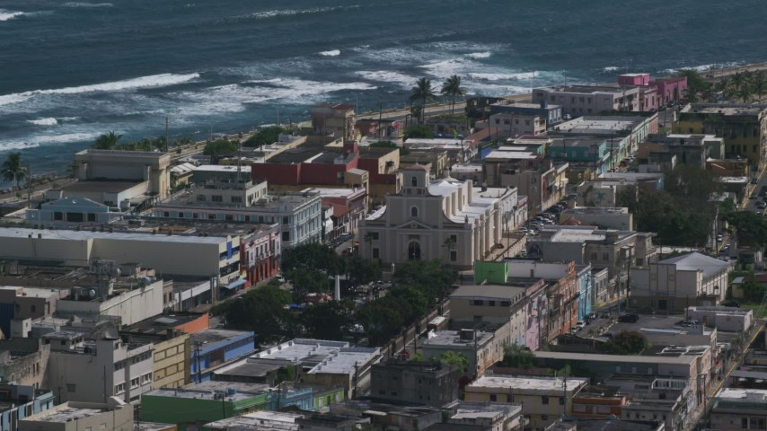 5k stock footage aerial video of the Catedral San Felipe among buildings along the coast, Arecibo Puerto Rico Aerial Stock Footage | AX101_137