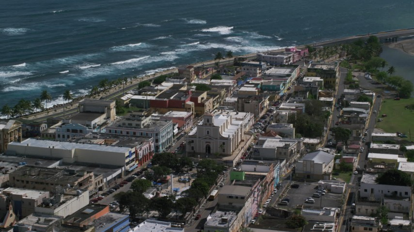 5k stock footage aerial video of Coastal buildings and tilt down on Catedral San Felipe, Arecibo Puerto Rico Aerial Stock Footage | AX101_138