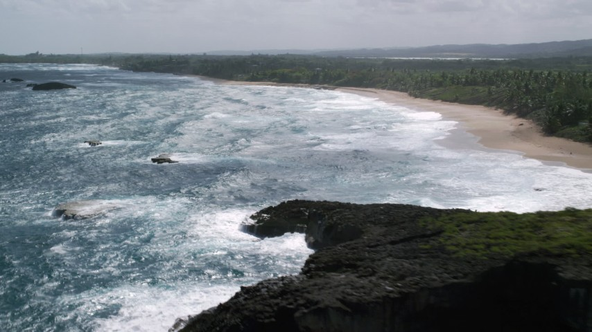5k stock footage aerial video Flying over blue waters toward the beach and tree lined coast, Arecibo, Puerto Rico Aerial Stock Footage | AX101_155