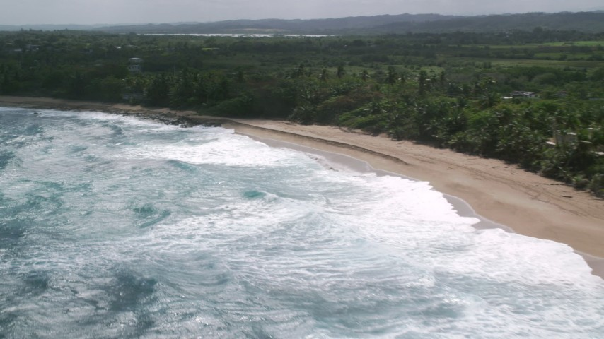 5k stock footage aerial video of Blue waters along a beach and tree lined coast, Arecibo, Puerto Rico Aerial Stock Footage | AX101_156
