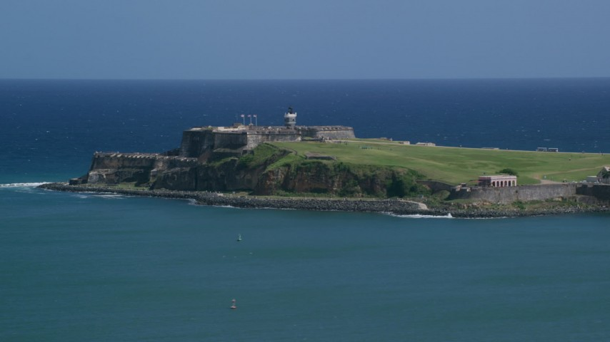 5k stock footage aerial video of Fort San Felipe del Morro surrounded by crystal blue waters, Old San Juan Puerto Rico Aerial Stock Footage | AX101_235