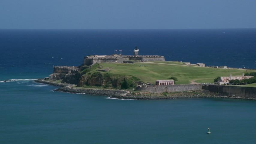 5K stock footage aerial video of the Back of Fort San Felipe del Morro in crystal blue waters, Old San Juan Puerto Rico Aerial Stock Footage | AX101_236