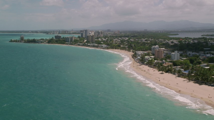 5k stock footage aerial video Flying along beachside coastal communities over crystal blue water, San Juan, Puerto Rico Aerial Stock Footage | AX102_006
