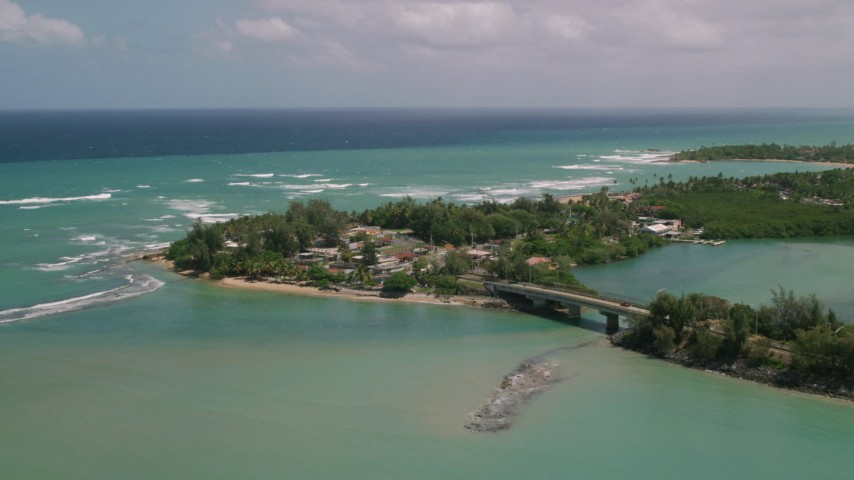 5k stock footage aerial video of Coastal shops and beach along crystal  turquoise waters, Loiza, Puerto Rico