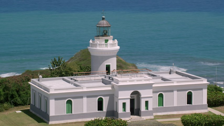 5k aerial video of Cape San Juan Light looking out on to crystal blue waters, Puerto Rico Aerial Stock Footage | AX102_066
