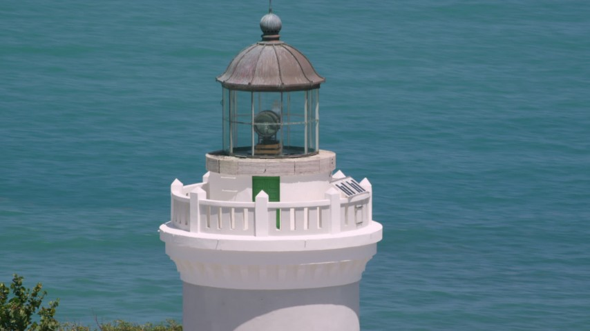 5k aerial video Orbiting the top of Cape San Juan Light with views of clear blue waters, Puerto Rico Aerial Stock Footage | AX102_070
