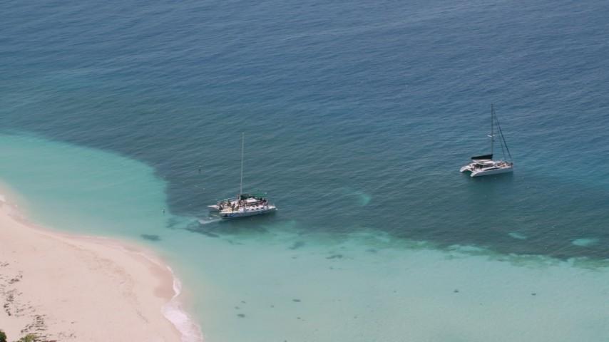 5k stock footage aerial video of Catamarans in clear blue tropical waters, Rada Fajardo, Puerto Rico Aerial Stock Footage | AX102_075