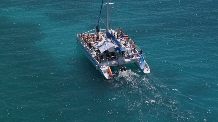 5k aerial video Flying away from a catamaran in tropical blue water, Rada Fajardo, Puerto Rico Aerial Stock Footage | AX102_077