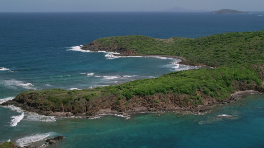 5k stock footage aerial video of a Rugged coastline of a tree covered island in blue waters, Culebra, Puerto Rico Aerial Stock Footage | AX102_108