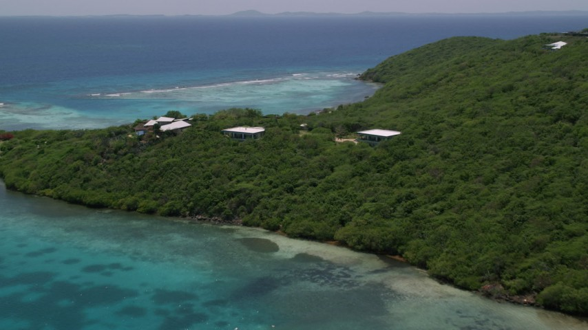 5k stock footage aerial video of Oceanfront homes nestled among trees along sapphire blue waters, Culebra, Puerto Rico  Aerial Stock Footage   AX102_137