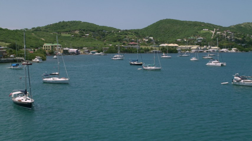 5k stock footage aerial video of Sailboats in sapphire waters approaching a coastal town, Culebra, Puerto Rico Aerial Stock Footage | AX102_162