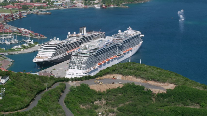 Docked cruise ship in a coastal town in sapphire waters, Charlotte Amalie, St. Thomas Aerial Stock Footage | AX102_199