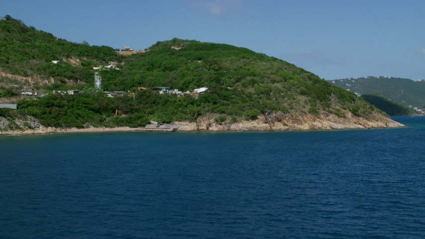 Approaching a coast in sapphire waters, Charlotte Amalie, St. Thomas Aerial Stock Footage | AX102_201