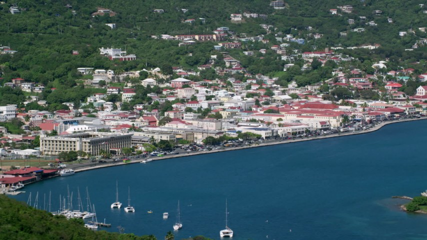 Houses in a coastal town along sapphire blue waters, Charlotte Amalie, St. Thomas  Aerial Stock Footage | AX102_205