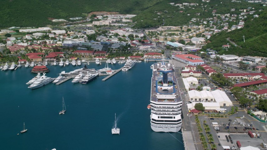 Cruise ship and yachts docked in sapphire waters along a coastal town, Charlotte Amalie, St. Thomas  Aerial Stock Footage | AX102_210