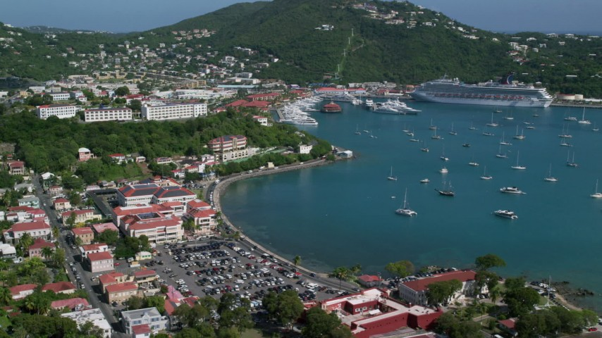 5k stock footage aerial video of Sailboats and cruise ship in sapphire blue waters along a coastal town, Charlotte Amalie, St Thomas Day Sunny Side View Aerial Stock Footage | AX102_224