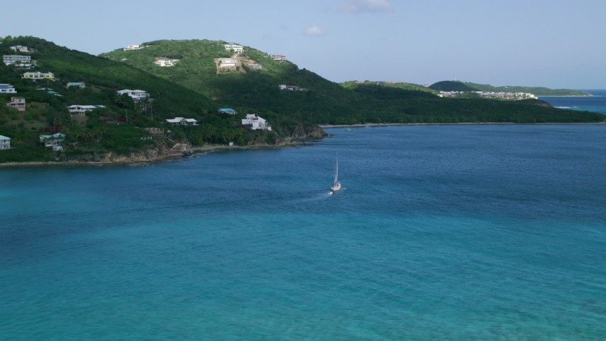 5k stock footage aerial video of a Sailboat in sapphire blue waters along oceanfront homes, Southside, St Thomas Aerial Stock Footage | AX102_234