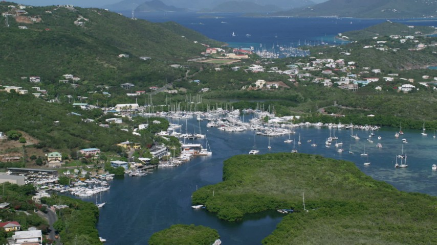 5k aerial video of a Marina with boats in blue ocean waters, Benner Bay, St Thomas Aerial Stock Footage | AX102_238