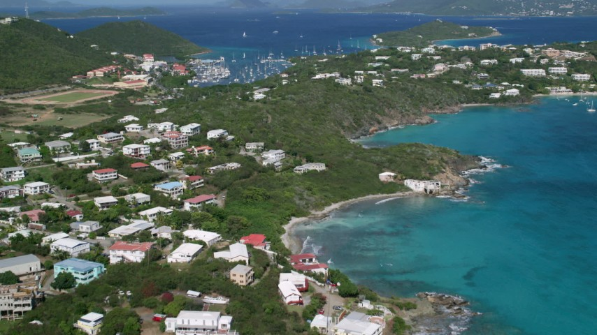 5k aerial video Flying over trees and homes surrounded by sapphire blue waters, Red Hook, St Thomas Aerial Stock Footage | AX102_240