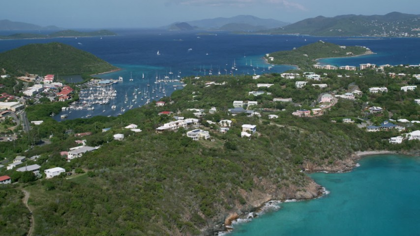 5k stock footage aerial video Flying over homes toward Caribbean blue waters, Red Hook, St Thomas Aerial Stock Footage | AX102_241