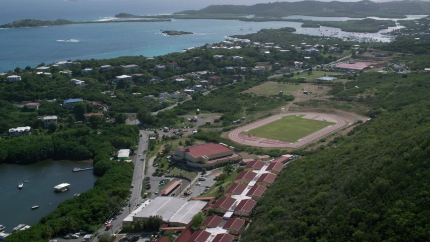 5k stock footage aerial video of a High school track field near blue coastal waters, East End, St Thomas Aerial Stock Footage | AX102_244
