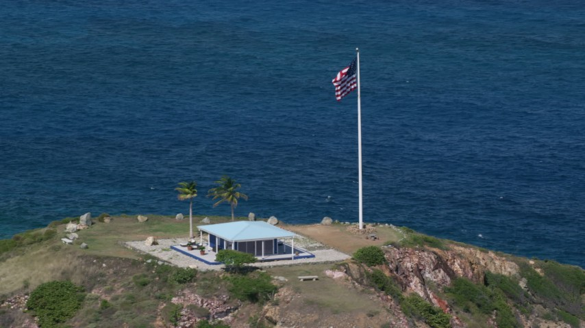 5k aerial video Orbiting an oceanfront guesthouse and American flag, Little St James Island, St Thomas Aerial Stock Footage | AX102_251