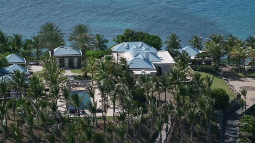 5k aerial video of an Oceanfront mansion and palm trees, Little St James Island, St Thomas Aerial Stock Footage | AX102_252
