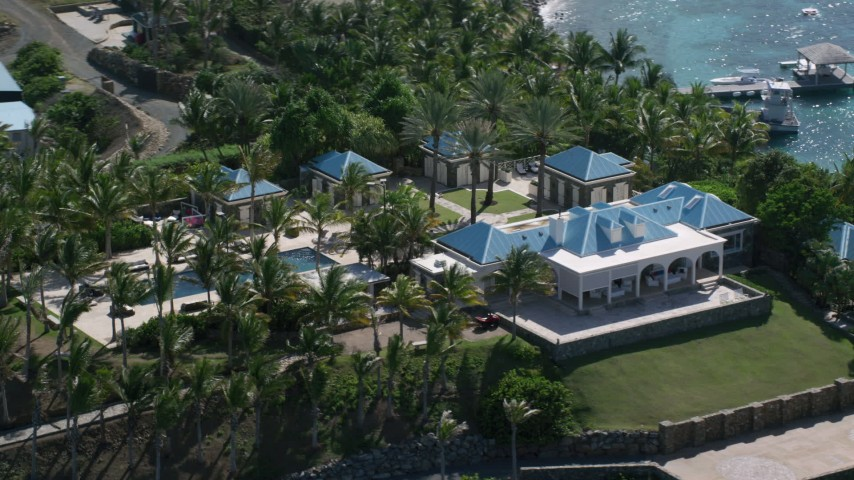 5k aerial video of an Oceanfront mansion and palm trees on turquoise blue waters, Little St James Island, St Thomas Aerial Stock Footage | AX102_253