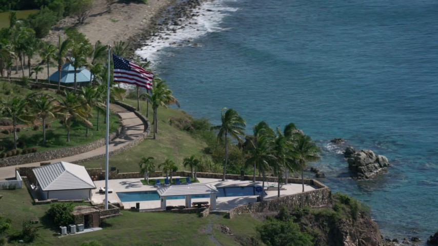 5k stock footage aerial video of an Oceanfront pool and American flag along Caribbean blue waters, Little St James Island, St Thomas  Aerial Stock Footage | AX102_254