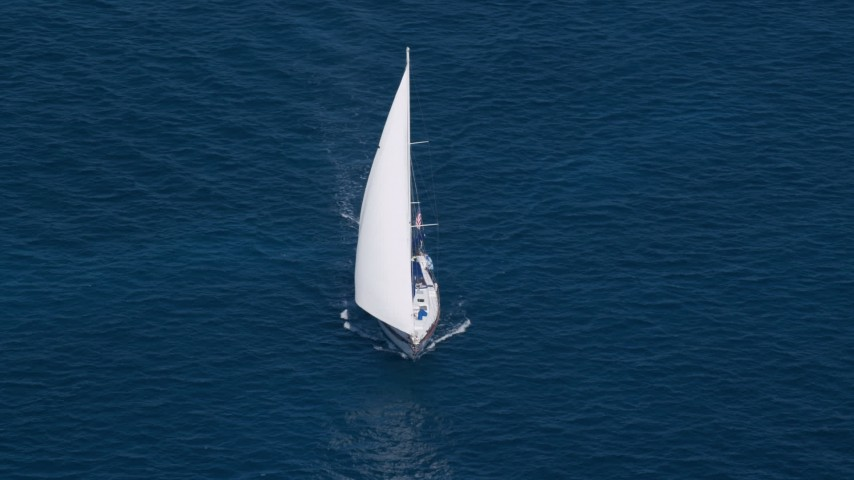 5k stock footage aerial video of a Sailboat in sapphire blue waters, St Thomas, USVI Aerial Stock Footage | AX102_256