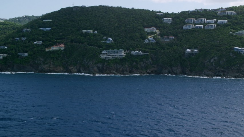 5k stock footage aerial video of a Hillside oceanfront homes along sapphire waters, Northside, St Thomas Aerial Stock Footage | AX102_262