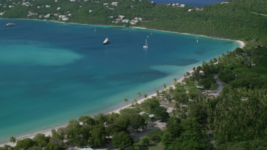 White sand Caribbean beach along turquoise blue waters with sailboats, Magens Bay, St Thomas Aerial Stock Footage | AX102_272