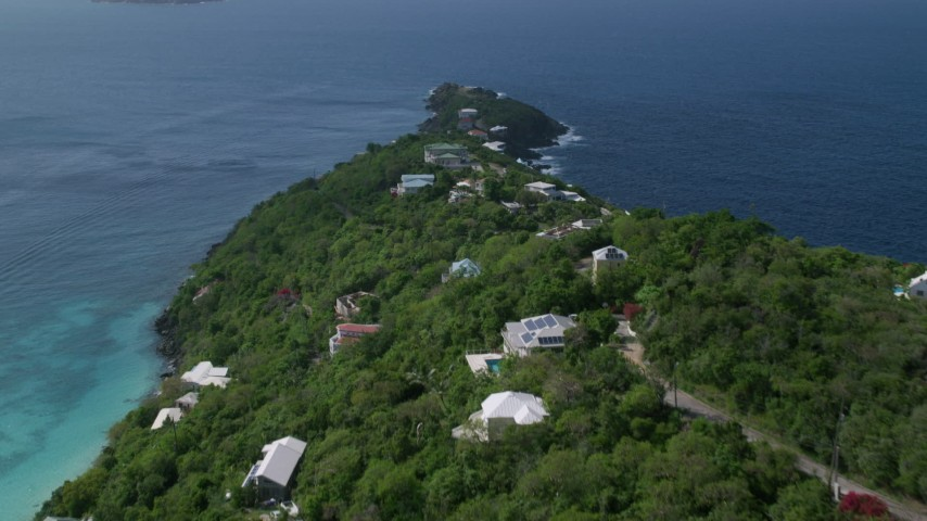 5k aerial video of Hillside oceanfront homes along sapphire blue Caribbean waters, Magens Bay, St Thomas Aerial Stock Footage | AX102_276