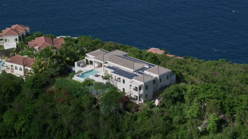 5k aerial video of a Hilltop mansion overlooking turquoise blue Caribbean waters, Magens Bay, St Thomas Aerial Stock Footage | AX102_286
