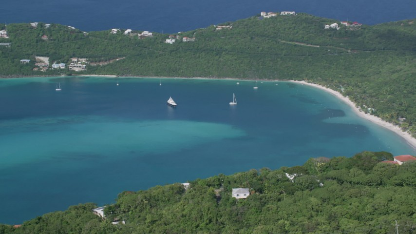 5k aerial video of a Caribbean beach against tree covered hillside and turquoise blue waters, Magens Bay, St Thomas  Aerial Stock Footage | AX102_301
