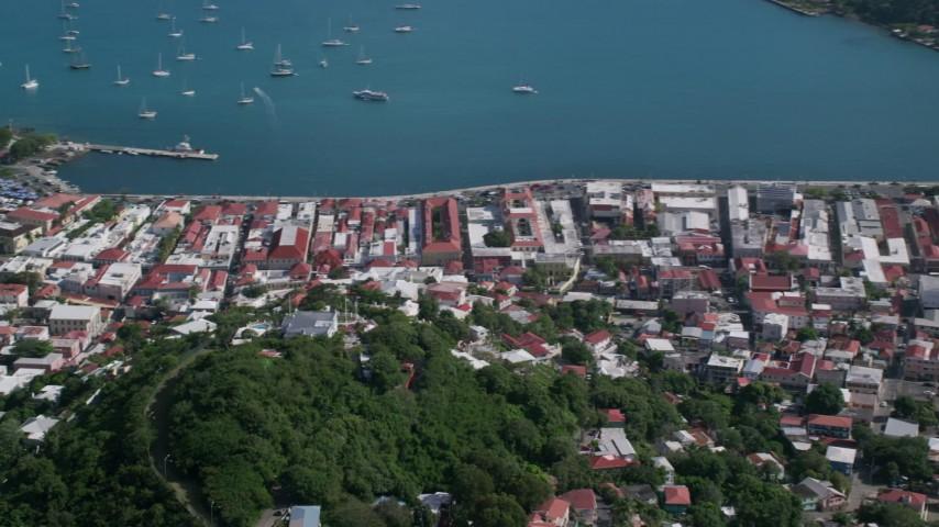 Coastal town along sapphire blue Caribbean waters, Charlotte Amalie, St Thomas Aerial Stock Footage | AX102_303