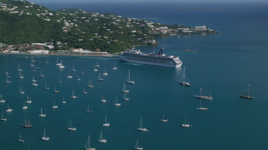 5k stock footage aerial video of a Cruise ship and sailboats in turquoise blue Caribbean waters, Charlotte Amalie, St Thomas Aerial Stock Footage | AX103_005