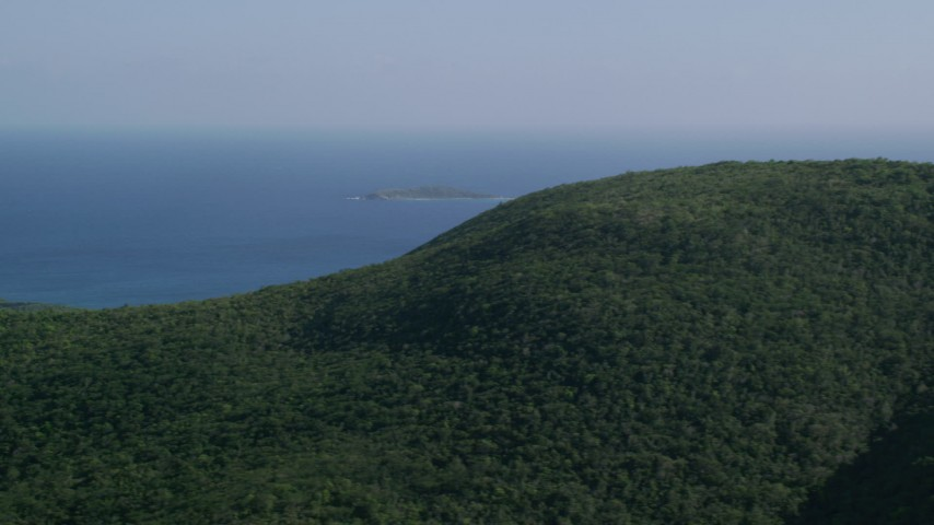 5k stock footage aerial video of Tree covered hills above blue Caribbean waters, Southside, St Thomas Aerial Stock Footage | AX103_010