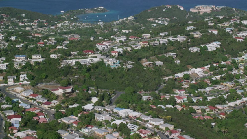 5k aerial video of Coastal homes among trees along Caribbean blue waters, East End, St Thomas Aerial Stock Footage | AX103_011