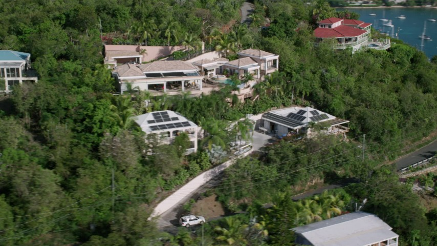 5k aerial video of Caribbean homes on a tree covered hillside over looking the ocean, Cruz Bay, St John Aerial Stock Footage | AX103_033