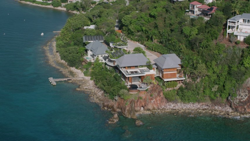 5k stock footage aerial video of an Oceanfront mansion along turquoise blue Caribbean waters, Cruz Bay, St John Aerial Stock Footage | AX103_034