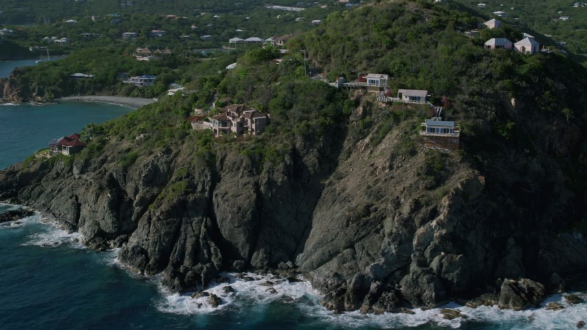 5k stock footage aerial video of a Cliff top mansions and sapphire blue Caribbean waters, Cruz Bay, St John Aerial Stock Footage | AX103_036