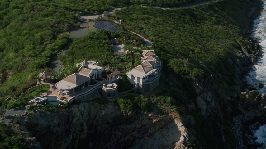 5k aerial video of a Cliff top mansion and Caribbean blue ocean view, Cruz Bay, St John Aerial Stock Footage | AX103_040