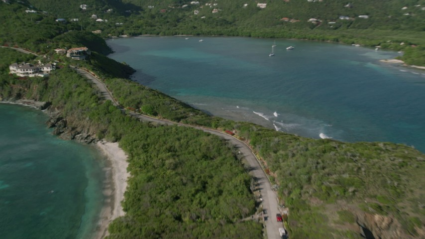 5k stock footage aerial video of a Coastal road and mansions with turquoise blue water on either side, Cruz Bay, St John Aerial Stock Footage | AX103_041