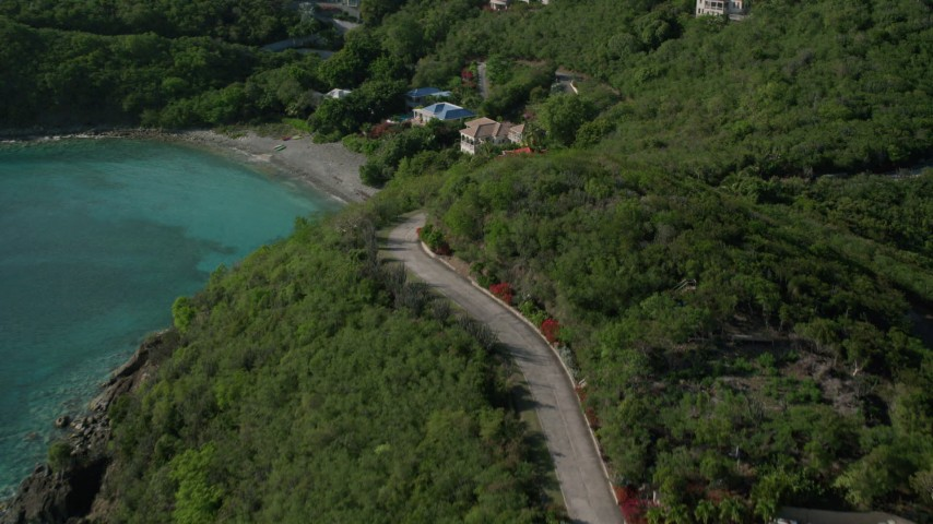 5k aerial video of a Coastal road and mansions along Caribbean blue waters, Cruz Bay, St John Aerial Stock Footage | AX103_042