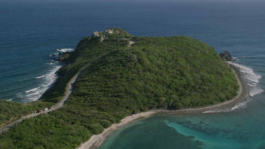5k aerial video of a Cliff top mansion among trees and sapphire blue Caribbean waters, Cruz Bay, St John Aerial Stock Footage | AX103_043